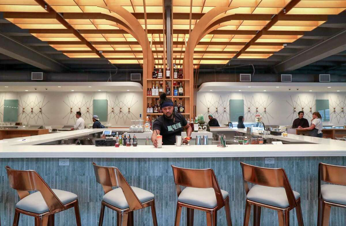 Amaud Butler serves a La Alondra cocktail at Politan Row, the new Rice Village food hall at 2445 Times Blvd. that features a bar and eight dining concepts under one roof.