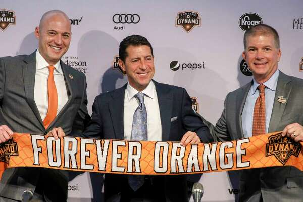 Matt Jordan, from left, senior vice president and general manager of the Houston Dynamo, Tab Ramos, Houston Dynamo head coach, and John Walker, president of business operations, pose for photos during a press conference at BBVA Stadium on Wednesday, Nov. 6, 2019, in Houston. The team formally introduced Ramos, who was previously the U.S. men's U-20 head coach.