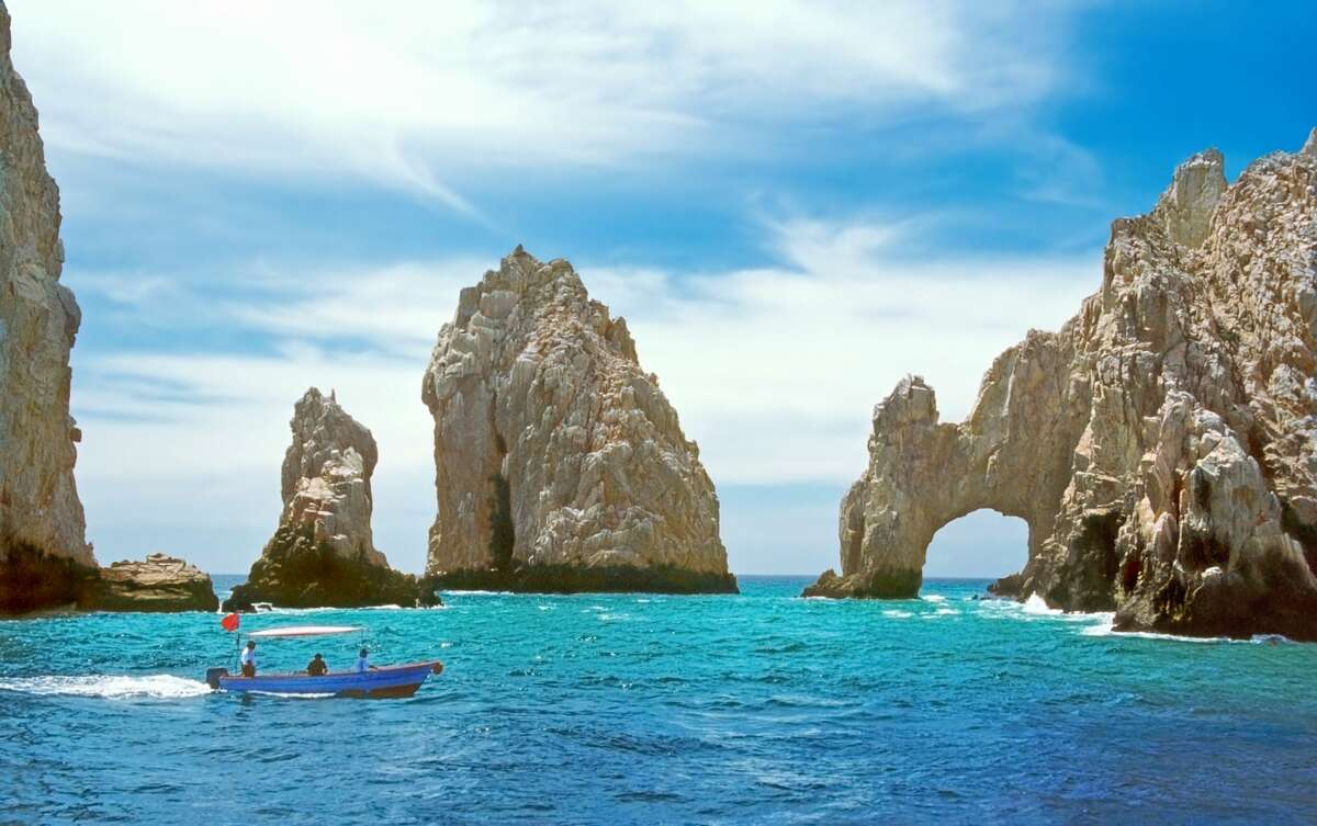 Inside the bay at Cabo San Lucas, a small tourboat is dwarfed by rock formations including the famous