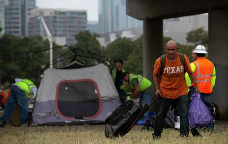 "Carlos, better known as ""El Tío,"" carries the belongings of a friend who lived under the Interstate 35 overpass and recently died, as a TxDOT cleanup crew disassembled the tent. Carlos has been homeless nearly three years."