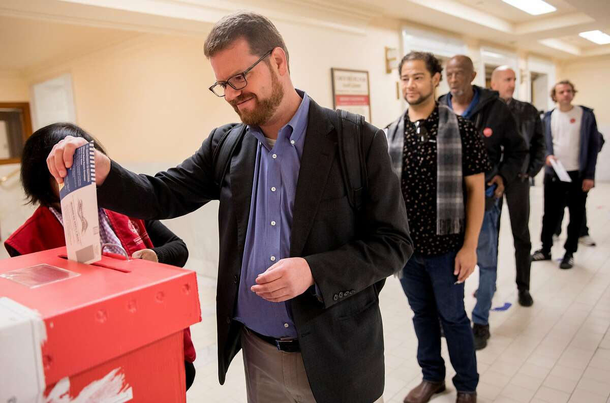 Hank Heckel places his ballot in the ballot box after voting at San Francisco City Hall in San Francisco, Calif. Tuesday, Nov. 5, 2019.