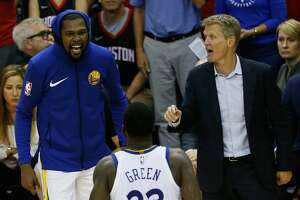 Head coach Steve Kerr, Kevin Durant #35 and Draymond Green #23 of the Golden State Warriors react in the fourth quarter of Game Seven of the Western Conference Finals of the 2018 NBA Playoffs against the Houston Rockets at Toyota Center on May 28, 2018 in Houston.
