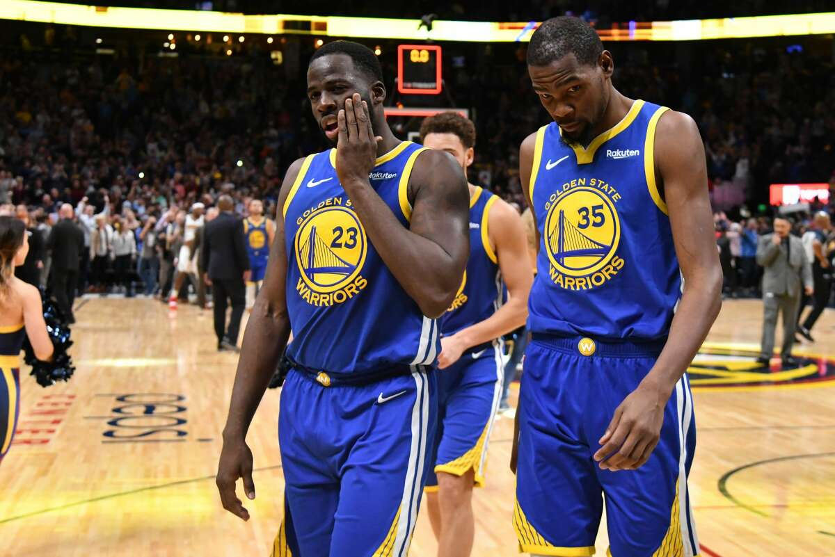 Draymond Green #23 and Kevin Durant #35 of the Golden State Warriors walk off the court after losing to the Denver Nuggets at Pepsi Center on October 21, 2018 in Denver.