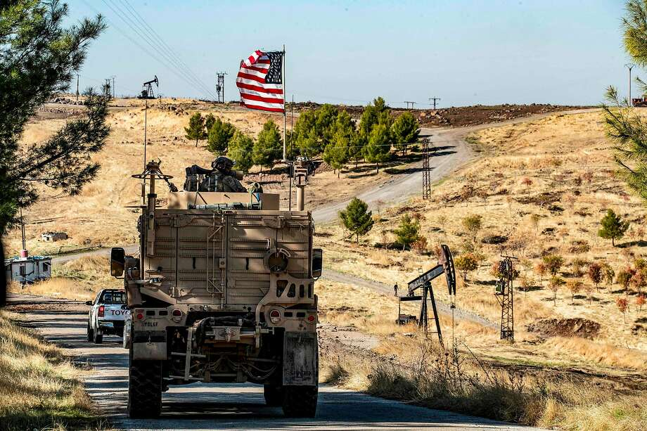 U.S. military armored vehicles patrol oil fields in Syria's northeastern Hasakeh province. Photo: Delil Souleiman / AFP Via Getty Images