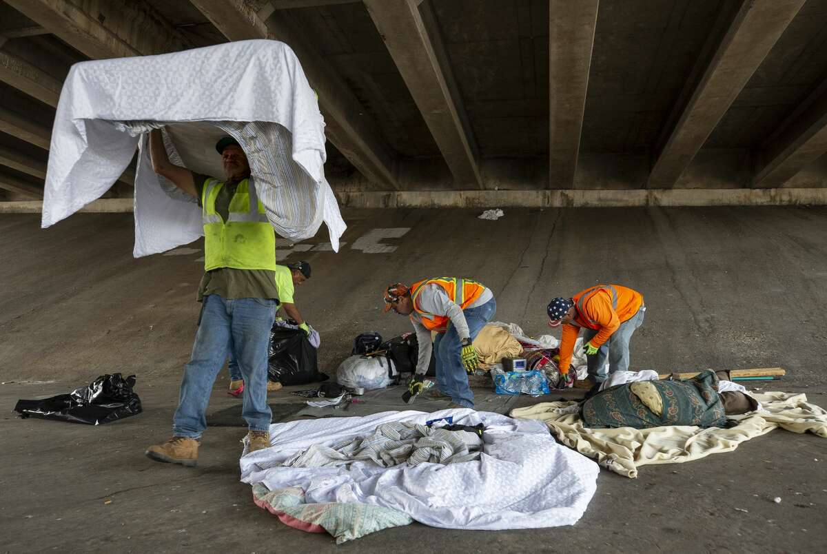 TxDOT crew members cleanup a homeless encampment under the Interstate 35 overpass Tuesday, Nov. 5, 2019, in Austin.