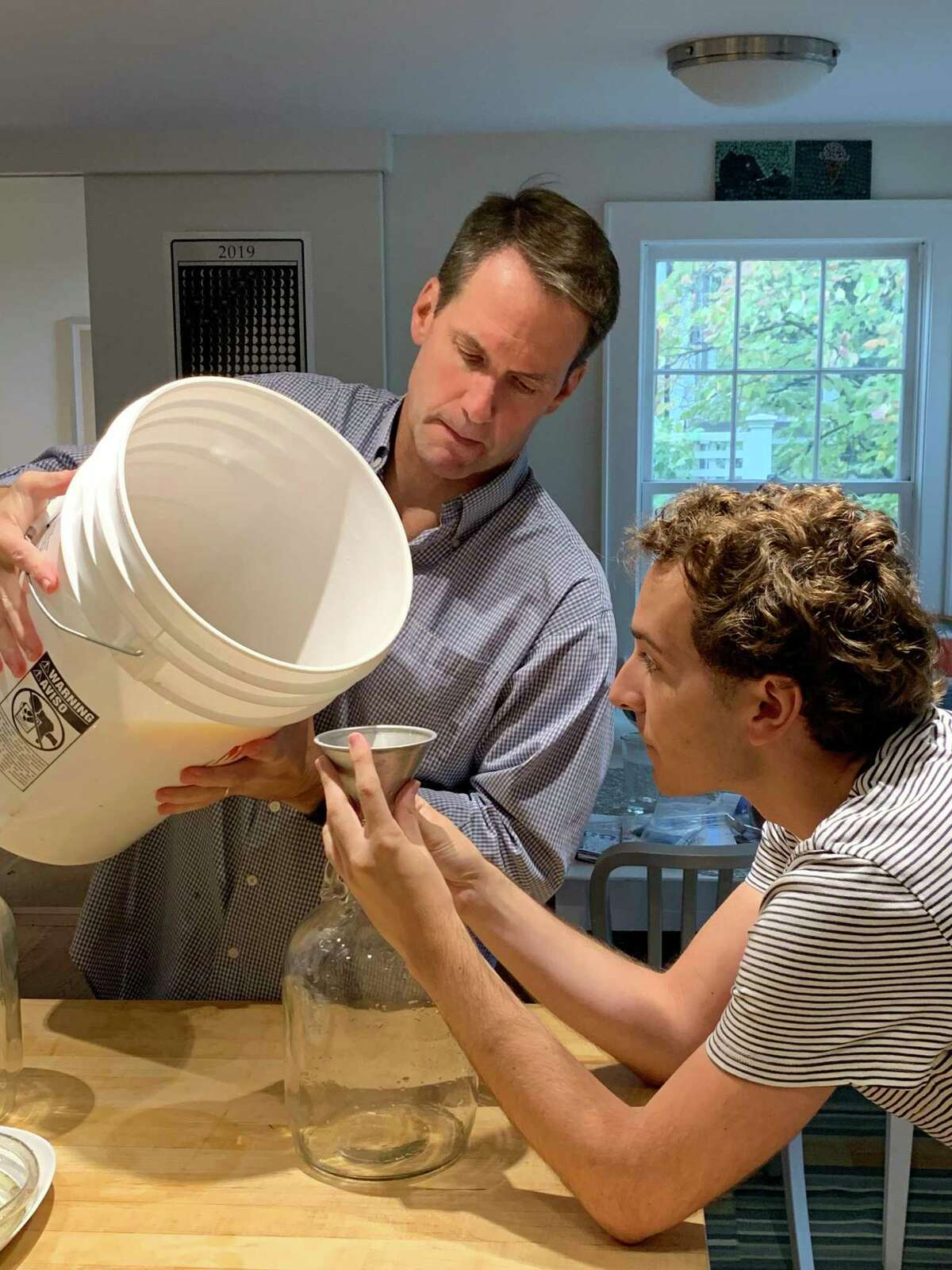 U.S. Rep. Jim Himes and Sen. Will Haskell starting a batch of cider to ferment.