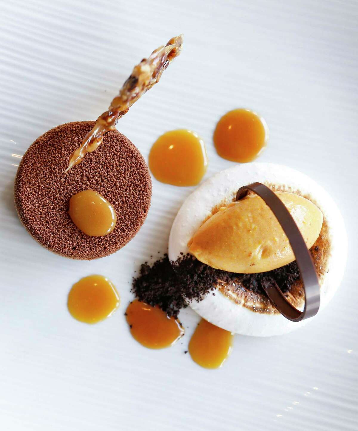 Pastel de Chocolate Criollo at Caracol is a chocolate mousse with bourbon-toffee sauce and toasted meringue served with pumpkin-orange ice cream.