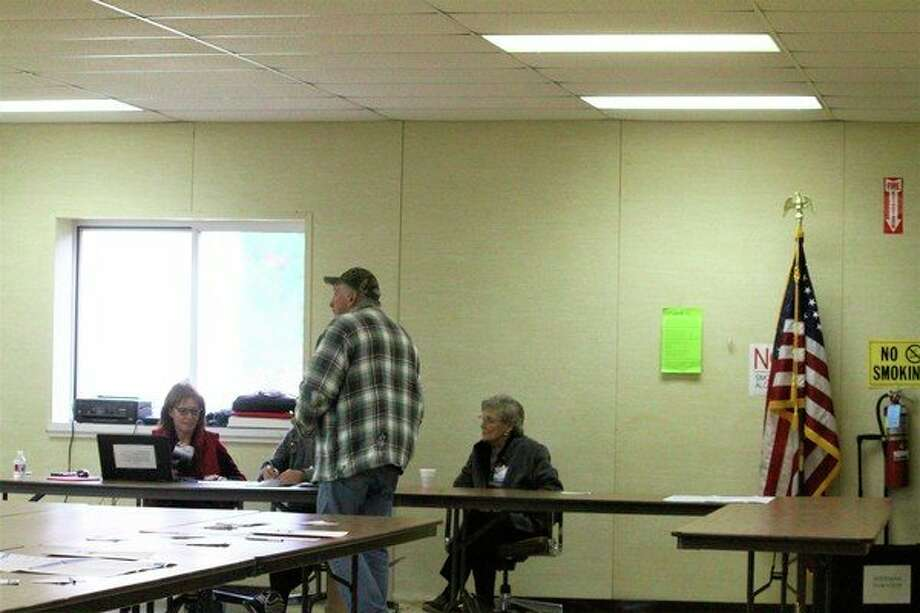 A voter gets ready to submit his ballot at Sherman Township Hall. 2,548 voters came out to voice their opinion on the topic. (Pioneer photo/ Catherine Sweeney)