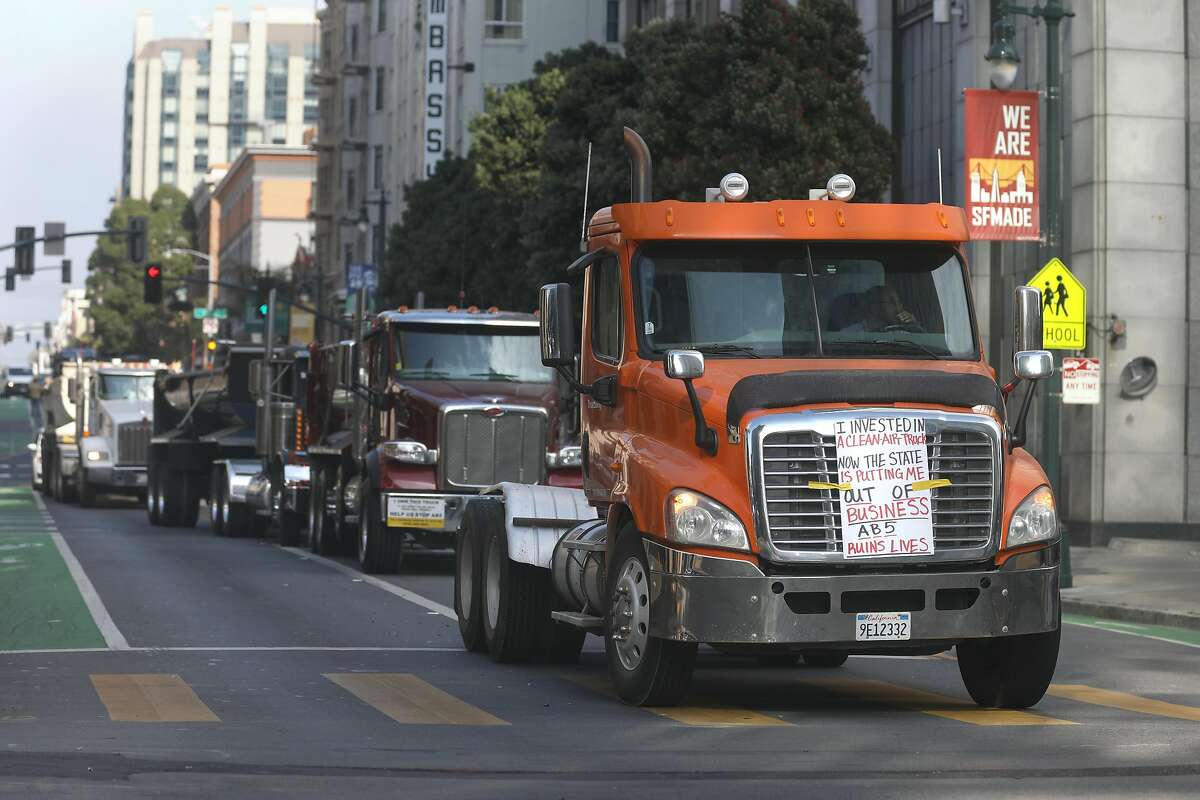 Trucks on Polk St. display signs in protest of AB5 on Wednesday, Nov. 6, 2019, in San Francisco, Calif.