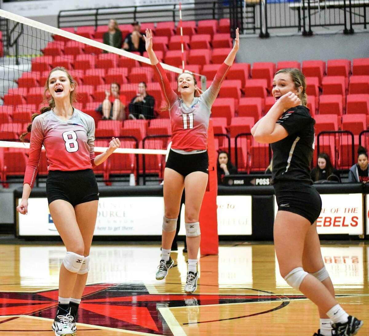 Hargrave's Laynee Beam (8), Kylie WIllis (11) and Kenzie Wiggins (black shirt) celebrate the Lady Falcons' victory over Hardin-Jefferson in the Bi-District playoff match at Lee College in Baytown on Nov. 5