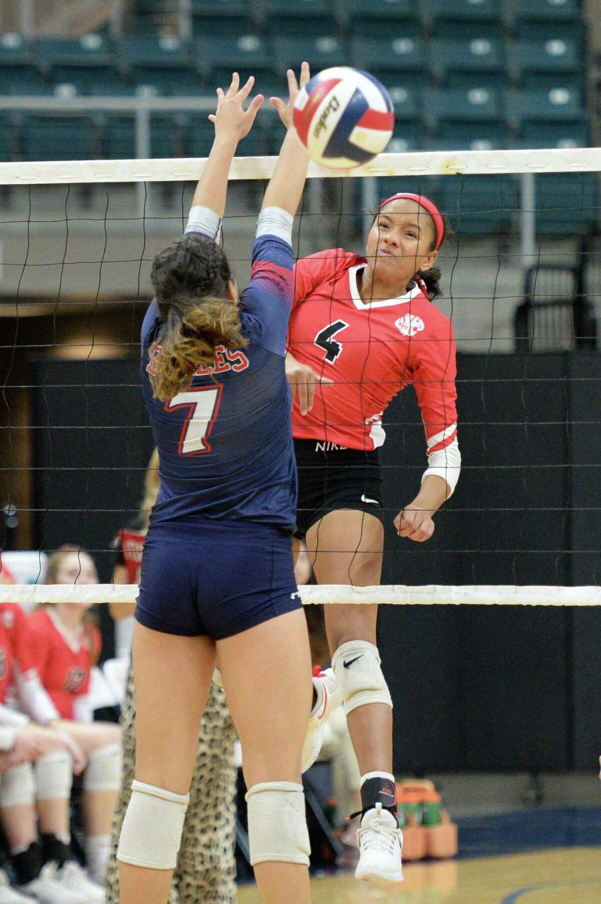 Perris Key (4) of Katy hits a kill shot past Renata Bolado Corona (7) of Dulles during the third set of a Class 6A Region III bi-district volleyball playoff match between the Dulles Vikings and the Katy Tigers on Monday, November 4, 2019 at the Leonard Merrell Center, Katy, TX.