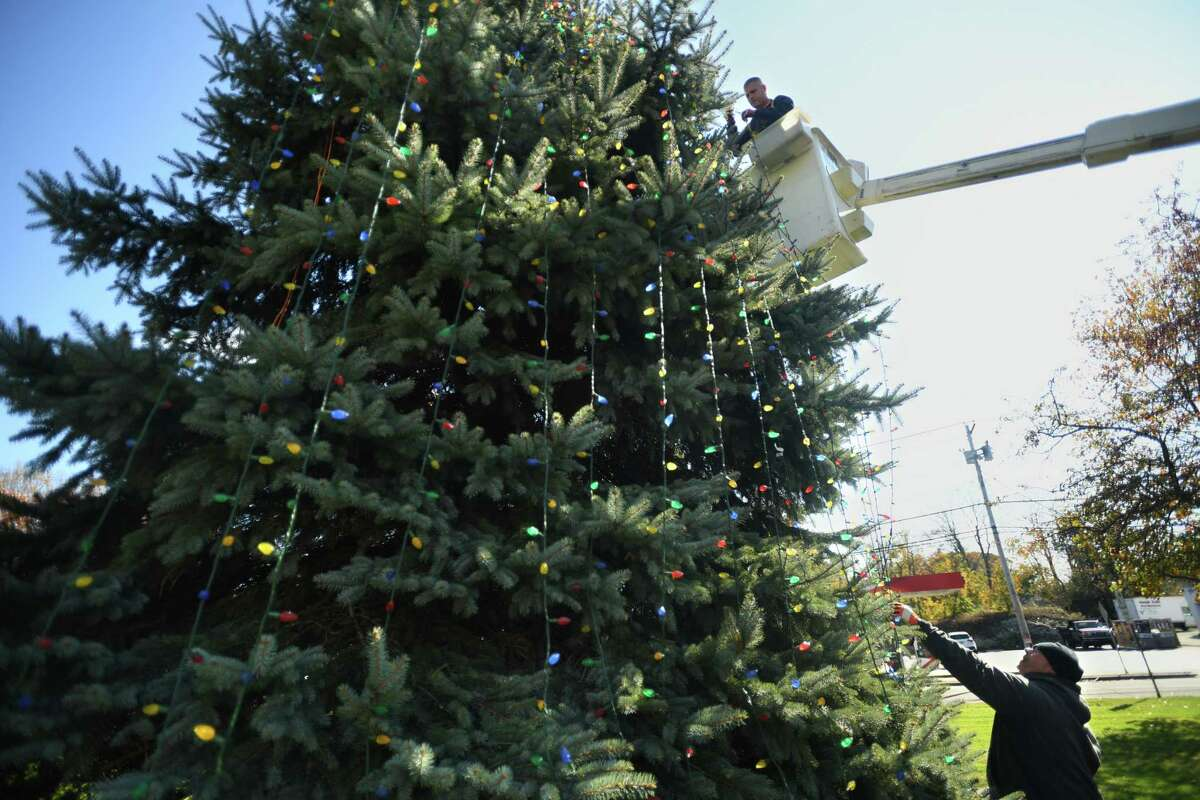 Milford Public Works employees string holiday lights on one of the many trees on the Milford Green in Milford Conn. on Wedesday, November 6, 2019.