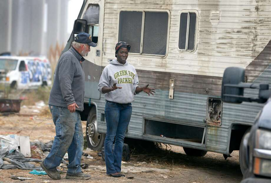 Kelly Thompson (left), who's lived in the homeless encampment on Wood Street for a year, helps Ieshia Moss pull her motor home out of a ditch at the camp in Oakland, Calif. on Tuesday, Nov. 5, 2019. Oakland officials have begun clearing out abandoned cars, motor homes and forcing the residents to leave in an overall effort to completely clear the lot and turn it into a safe parking zone. Photo: Paul Chinn / The Chronicle