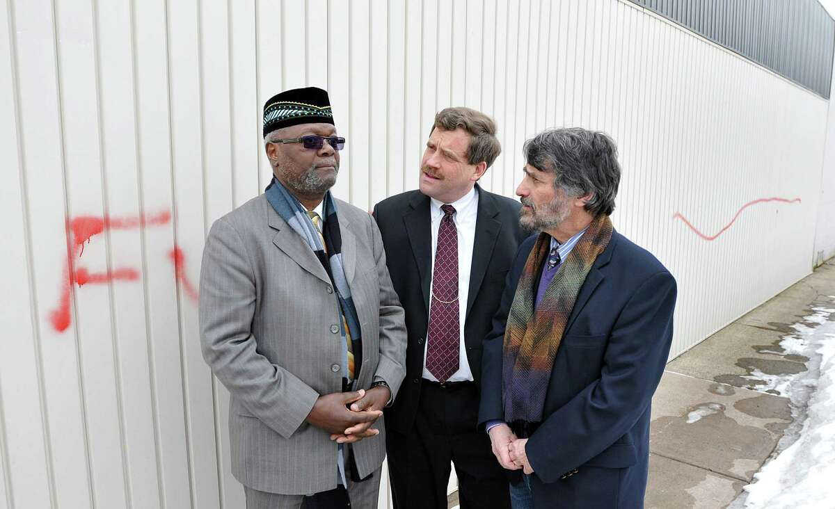 Imam Abdul-Majid Karim Hasan, left, talks with the Rev. Scott Morrow of North Haven Congregational Church, center, and Rabbi Herbert Brockman, then of Congregation Mishkan Israel, outside the Islamic center that was defaced by graffiti in 2011.