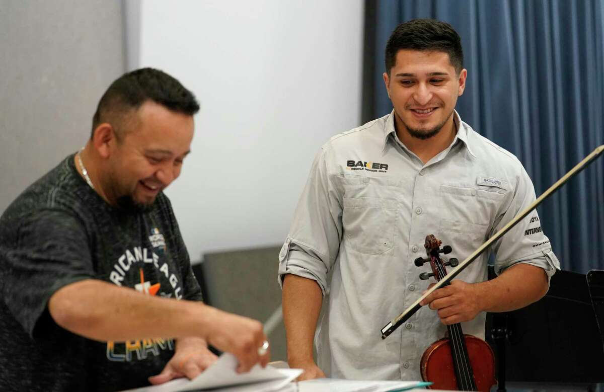Jose Longoria, left, director of Mariachi Pumas, looks for sheet music to give to violinist Jose Pineda during the Mariachi Pumas rehearsal at University of Houston Tuesday, Oct. 22, 2019, in Houston.