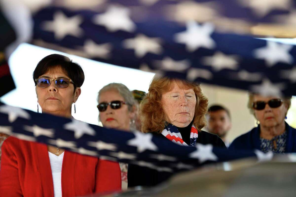 People listen during a service for two Marine Corps veterans, Gil Vargas, 65, and Alberto Vasquez, 67, and Army veteran John J. Flynn, 61, during their burial service at Fort Sam Houston National Cemeter last February. The veterans left no known relatives, but more than 100 people attended. A series of Veterans Day events are planned this weekend and Monday in the San Antonio area.
