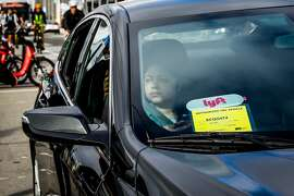 A woman looks out from a Lyft car outside the Cal Train station on Townsend Street in San Francisco, California, on Monday, May 20, 2019. Both Uber and Lyft have agreed to a 3.25%-per ride tax in an effort to avoid a tax on their gross receipts. The taxes will generate an estimated $30 million to $35 million for transportation improvements and street-safety upgrades.