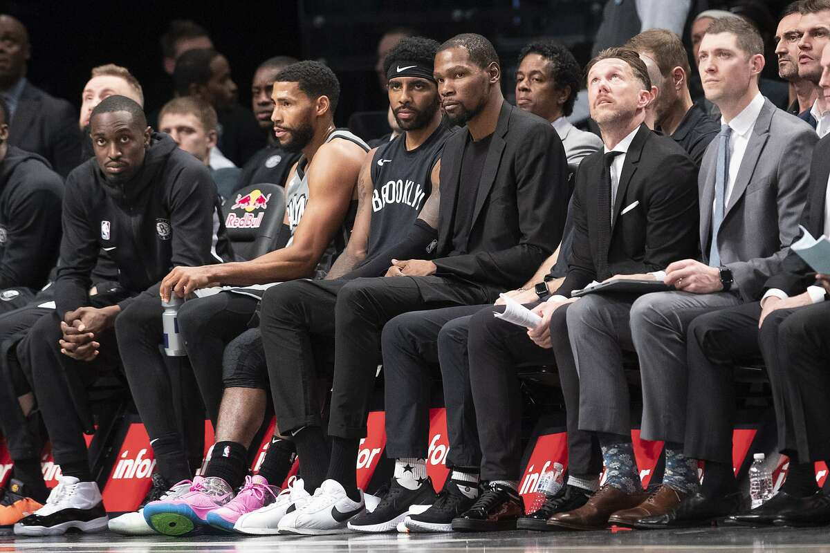 Brooklyn Nets guard Kyrie Irving, center left, and forward Kevin Durant, center right watch the action from the bench during the second half of an NBA basketball game against the New Orleans Pelicans, Monday, Nov. 4, 2019, in New York. (AP Photo/Mary Altaffer)