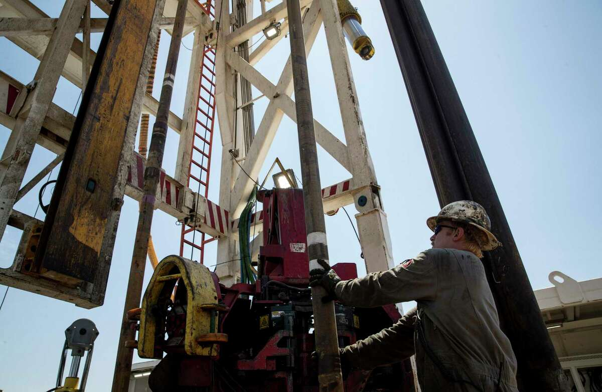 In this file photo, Caleb Adair, a floorhand from Booneville, Ark., builds stands on a drilling rig near Malaga, N.M. The oil industry has recovered since its worst days in April.