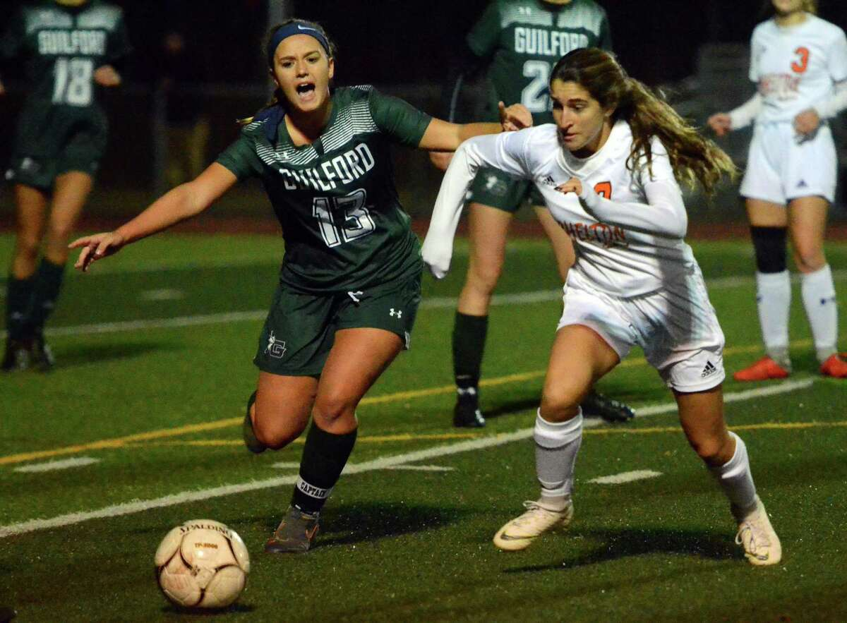 Guilford's Madison Gambardella (13) and Shelton's Mia Ferreira chase down the ball during girls soccer action in Fairfield on Oct. 31.
