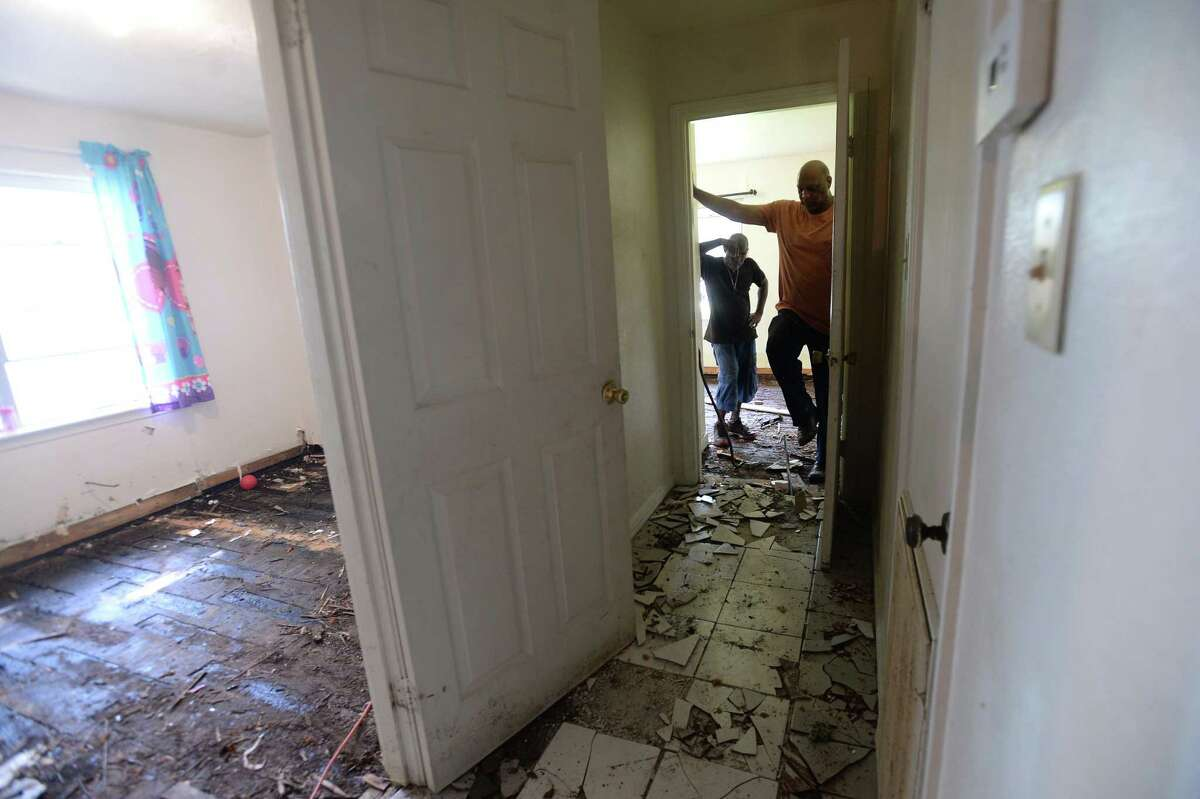Anthony Allen (left) and Robert Walker stop to take in the progress as they gut a property Walker owns on Skipwith Street as residents throughout flooded Beaumont neighborhoods get to the work of gutting their damaged homes Tuesday. Photo taken Tuesday, September 24, 2019 Kim Brent/The Enterprise