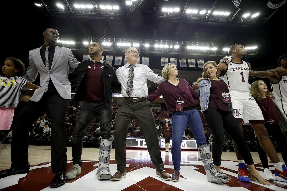 Texas A&M head coach Buzz Williams, center, sings the Aggie War Hymn with his family and staff members after defeating Northwestern State in an NCAA college basketball game Wednesday, Nov. 6, 2019, in College Station, Texas. (AP Photo/Sam Craft)