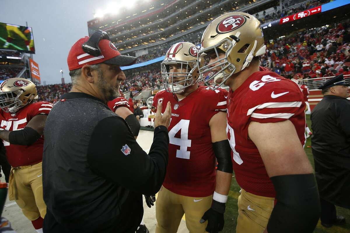 FILE: Offensive Line Coach John Benton, Joe Staley #74 and Mike McGlinchey #69 of the San Francisco 49ers talk on the sideline during the game against the Seattle Seahawks at Levi's Stadium on December 16, 2018 in Santa Clara.