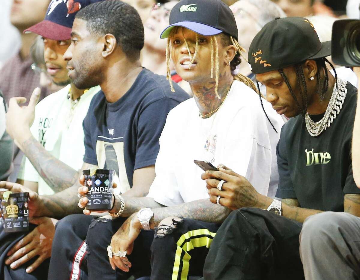 Travis Scott, far right, looks at his phone while on the sidelines as the Houston Rockets host the Golden State Warriors in the second half of game action at the Toyota Center on Wednesday, Nov. 6, 2019 in Houston.