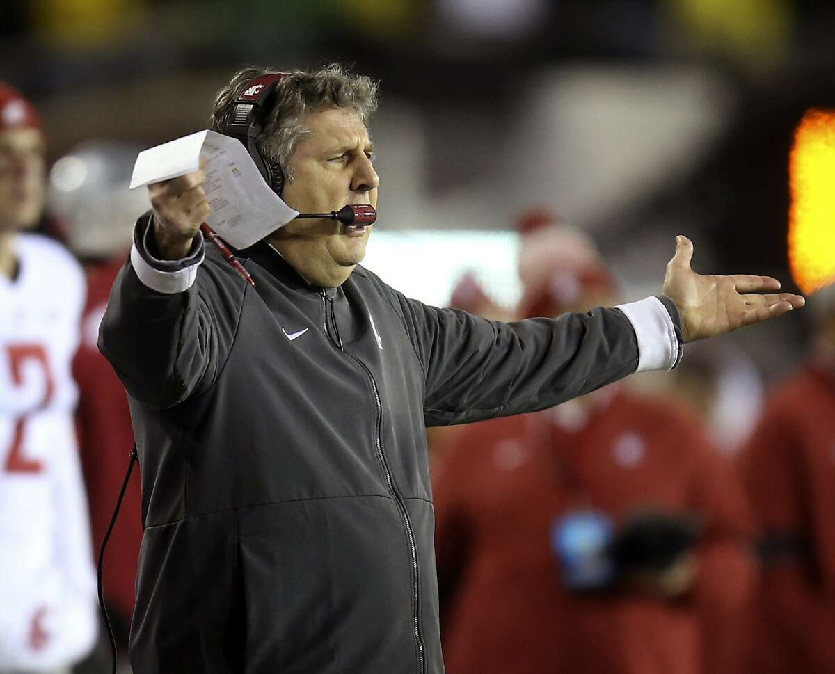 Washington State head football coach Mike Leach gestures to his team after a penalty call.