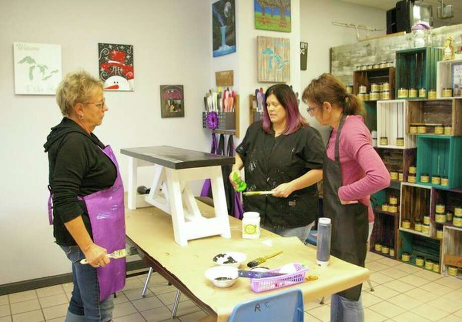 Owner of Purple Palette art studio in Auburn, Joyce Hamilton, center, shares a painting technique with Nancy Talaga-Brown of Saginaw, left, and Pam Talaga of Freelend, right. (Photo by Niky House)