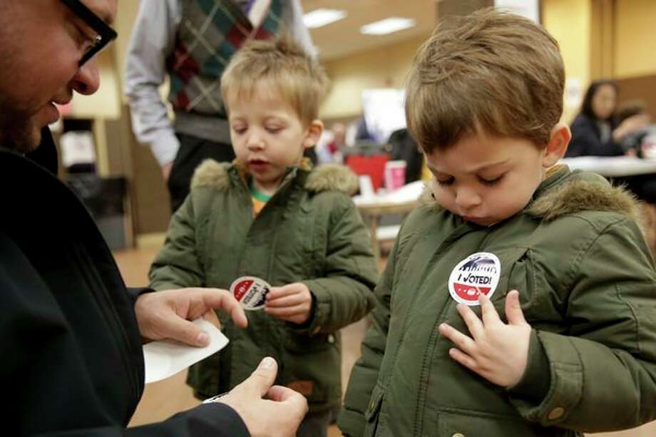 "Twins Amir, right, and Milo Klatzkin, 3, put on their ""I Voted"" stickers after their father Barry Klatzkin, left, voted at a polling site in New York, Tuesday. (AP Photo/Seth Wenig) / Copyright 2019 The Associated Press. All rights reserved."