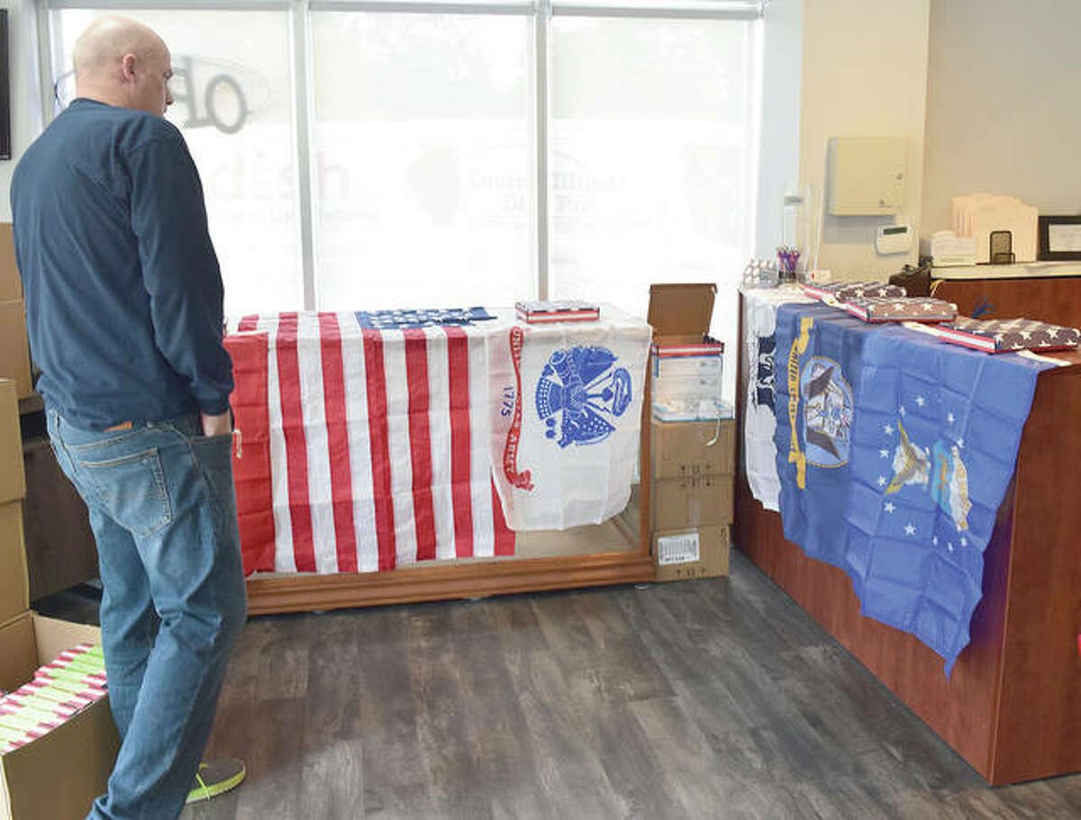 Tim Birdsell, owner of Central Illinois Dish Pro, takes a look at some of the flags he has bought to give away on Veterans Day to veterans and active-duty military.