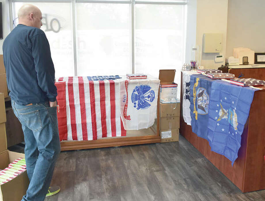Tim Birdsell, owner of Central Illinois Dish Pro, takes a look at some of the flags he has bought to give away on Veterans Day to veterans and active-duty military. Photo: Marco Cartolano | Journal-Courier