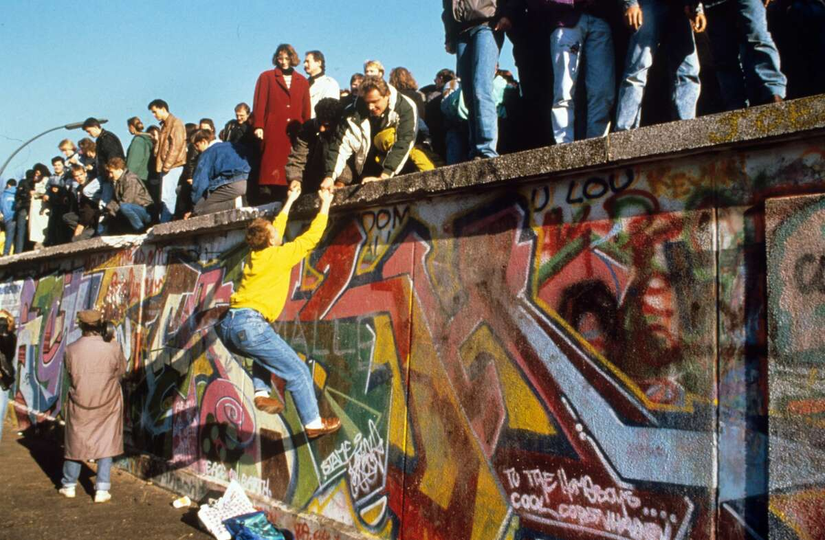 Two men on the Berlin Wall are helping a young man to climb up on 10 November 1989 in Berlin (Germany). The doom of the SED Regime has led to the rapid fall of the Berlin Wall on 9 November 1989. | usage worldwide (Photo by dpa/picture alliance via Getty Images)
