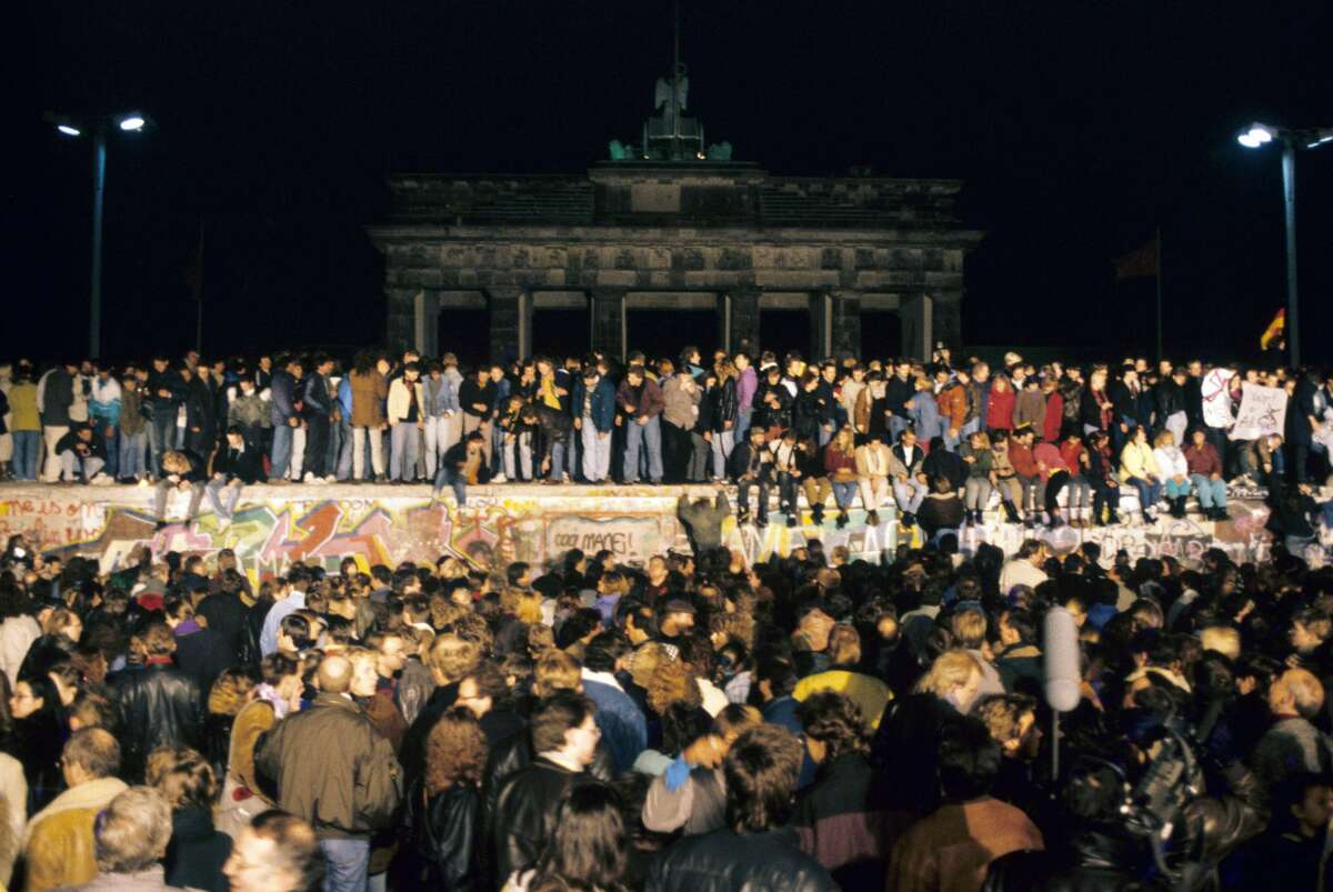 A huge crowd of people gathered on and in front of the Wall at Brandenburg Gate in Berlin on the evening of 10 November 1989. After the opening of some of the inner-German border crossings, some 50.000 GDR citizens visited West Berlin that night. | usage worldwide (Photo by dpa/picture alliance via Getty Images)