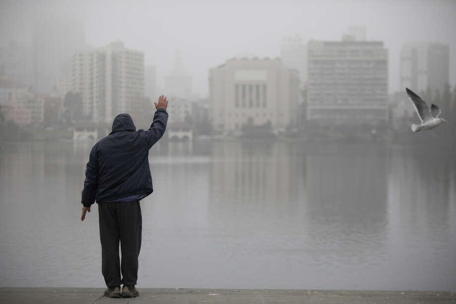 A man does exercises near Lake Merritt. A thick layer of fog coated Oakland on Thursday morning, Nov. 7, 2019. Photo: Douglas Zimmerman/SFGate.com