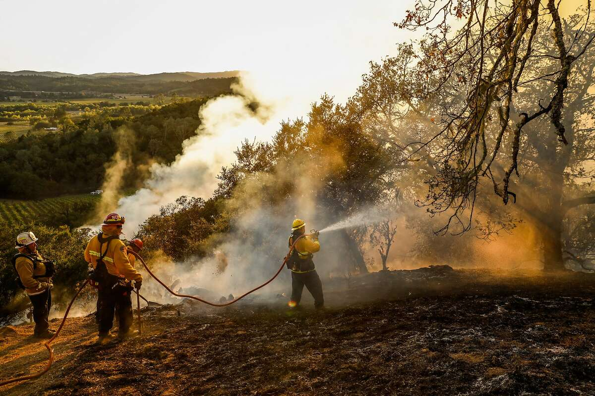 Marin County Strike team, including Carlos Gonzelez (right) create a fire break as the protect homes during the Kincade Fire in Geyserville, California, on Thursday, Oct. 24, 2019.