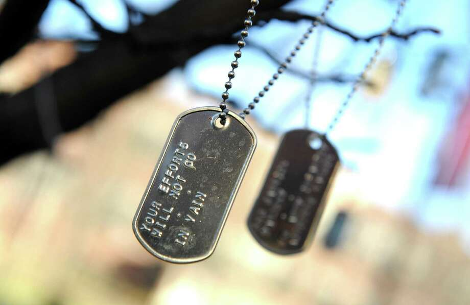 Dog tags made by students and community members and dedicated to specific service members , hang from a tree in the Quad area of the midtown campus of Western Connecticut State University in Danbury, Wednesday, Dec. 16, 2015. They were placed there during a Veterans Day ceremony in November. According to the university, the tree stands as a reminder of the bond the citizens of the United States share with the men and women of the Armed Forces. Photo: Carol Kaliff / Hearst Connecticut Media / The News-Times