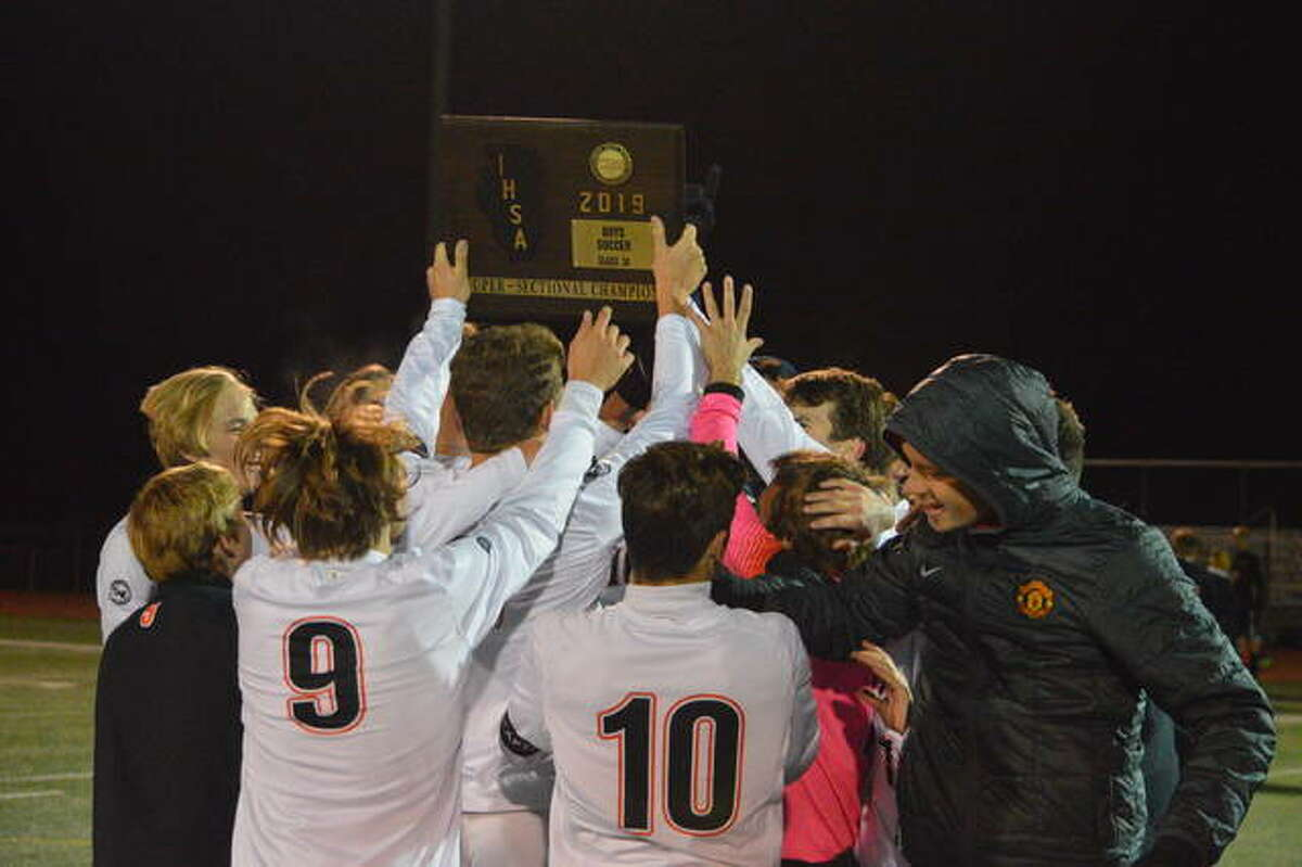 The Edwardsville Tigers celebrate with the Class 3A Bradley-Bourbonnais Super-Sectional plaque after defeating Lincoln-Way West.
