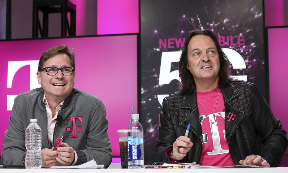 IMAGE DISTRIBUTED FOR T-MOBILE -  Un-carrier President Mike Sievert and CEO John Legere answer caller questions during the announcement of the future New T-Mobile's Un-carrier Moves on Thursday, Nov. 7, 2019, in New York. The Un-carrier unveiled three new initiatives for the proposed combination of T-Mobile and Sprint including the Connecting Heroes Initiative, a 10-year commitment to providing free unlimited talk, text and smartphone data for public and non-profit U.S. state and local law enforcement, fire and EMS agencies. (Brian Ach/AP Images for T-Mobile) Photo: Brian Ach, Associated Press