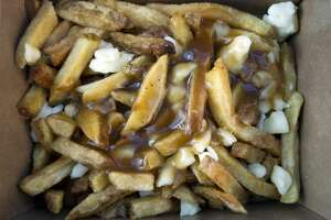 09/24/11 - TORONTO, ONTARIO - Poutine, dripping in gravy, ready to be consumed. Two contests for competitive eating, one for amateurs and one for professionals, took place outside Rogers Centre. The contest, hosted by Major League Eating, involved a poutine eating contest with Smoke Poutinerie supplying the fries and curd and gravy dishes for the competition. (Photo by Rick Madonik/Toronto Star via Getty Images)