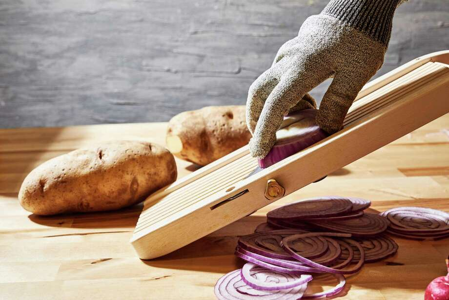 A mandoline slices faster and easier than a knife - if you know how to use it. Photo: Photo By Stacy Zarin Goldberg For The Washington Post. / For The Washington Post