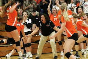 Greenfield coach Tyann Hallock (middle) welcomes her team back to the bench after Waterloo Gibault called timeout with the Tigers leading 11-6 in the third set Wednesday night in a Class 1A sectional title match in Raymond. The Tigers came out from the break and extended their lead to 15-6 and won their first sectional championship since 2007.