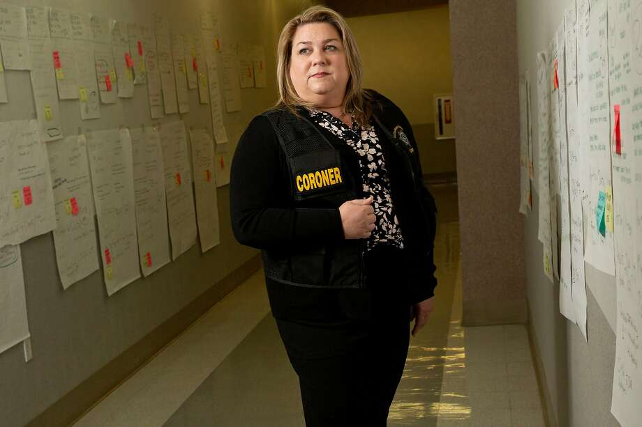 A portrait of Sacramento County Coroner Kimberly Gin on Tuesday, Feb. 19, 2019, in Sacramento. Since the 2018 Camp Fire, Gin and her team use the walls in this Sacramento County Coroner's Office hallway to keep information organized to identify the people killed in the fire. Each poster represents a person. The posters on Gin's left are of those still unidentified. Photo: Santiago Mejia / The Chronicle