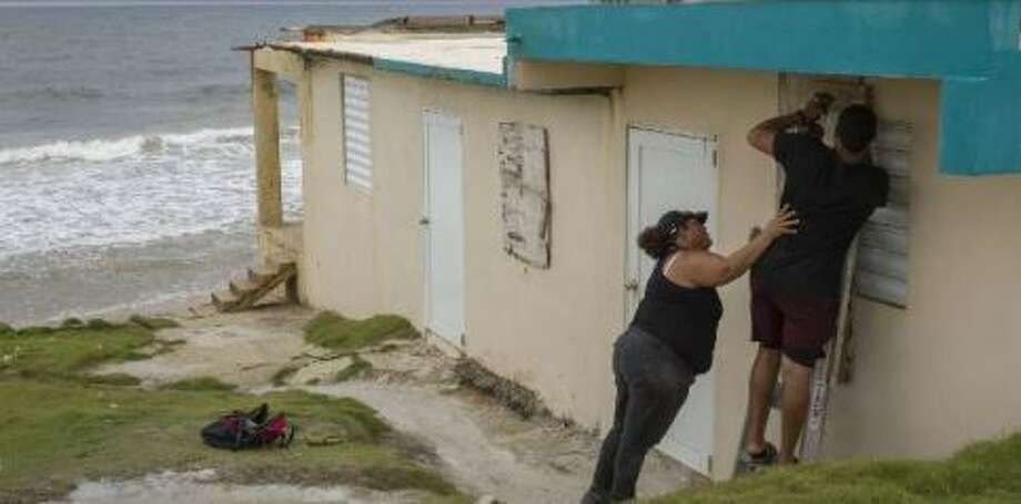 Ya Mary Morales (L) and Henry Sustache put plywood over the windows of their home as they prepare for the arrival of Tropical Storm Dorian on August 28, 2019 in Yabucoa, Puerto Rico. Photo: Joe Raedle/Getty Images