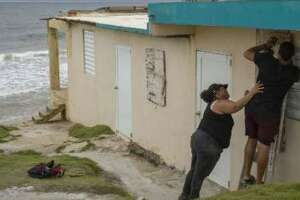 Ya Mary Morales (L) and Henry Sustache put plywood over the windows of their home as they prepare for the arrival of Tropical Storm Dorian on August 28, 2019 in Yabucoa, Puerto Rico.