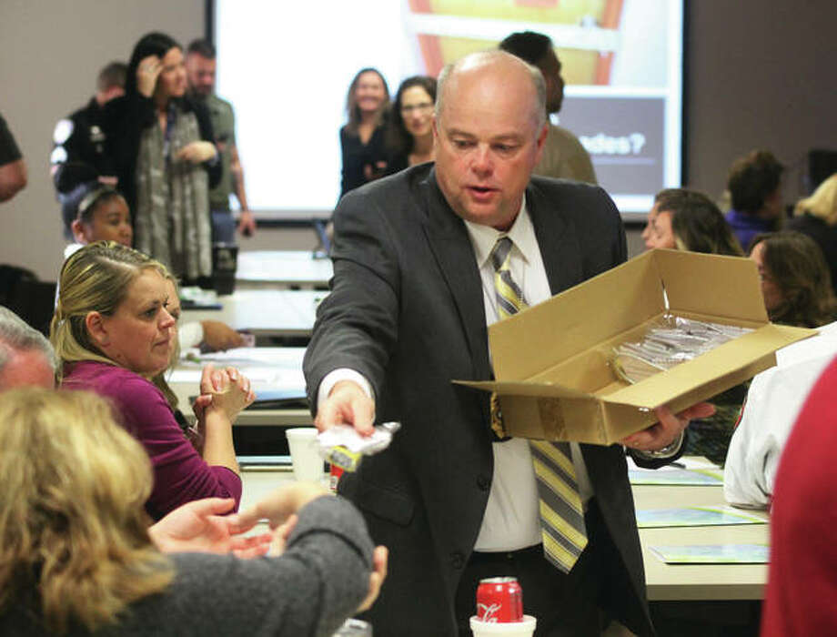 Alton Police Chief Jason Simmons hands out gun locks during an active shooter training program at OSF Saint Anthony's Hospital Thursday. The training was part of the hospital's ongoing Healthy Workplace initiative.