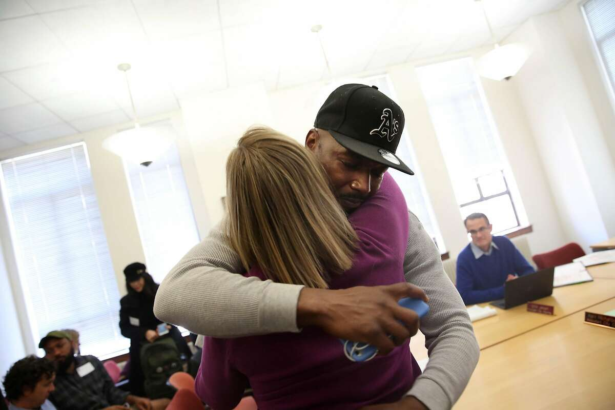 John Jones III (back), director of community and political engagement Just Cities and who was formerly incarcerated, gets a hug from Berkeley council member Kate Harrison (front) after the committee voted to support an ordinance aimed at improving the quality of life for formerly incarcerated people that was discussed on Thursday, November 7, 2019 in Berkeley, Calif.