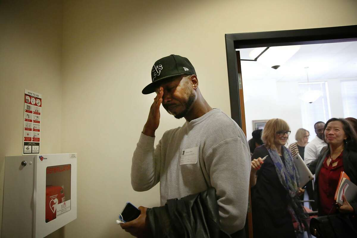 John Jones III (left), director of community and political engagement Just Cities and who was formerly incarcerated, wipes tears away as he leaves a the Berkeley City Council Land Use, Housing and Economic Development meeting after the committee voted to support an ordinance aimed at improving the quality of life for formerly incarcerated people that was discussed on Thursday, November 7, 2019 in Berkeley, Calif.