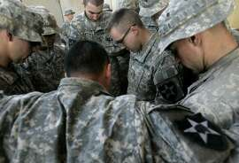 U.S. army soldiers from Blackfoot Company, 2nd Battalion, 23rd Infantry Regiment, pray before Christmas lunch at K-wal combat outpost in the village of Shakarat, in the volatile Diyala province, about 90 kilometers (60 miles) north of Baghdad, Iraq, Tuesday, Dec. 25, 2007. (AP Photo/Marko Drobnjakovic)